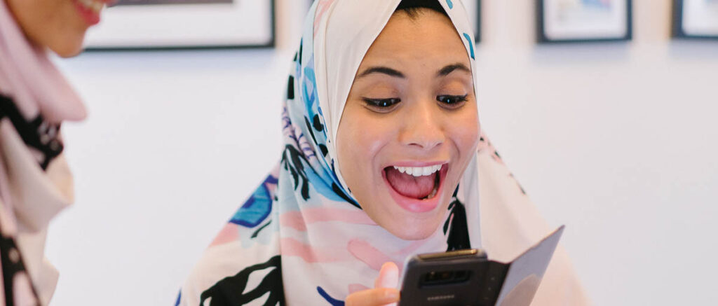 woman in hijab reading a blog post on her cell phone and smiling