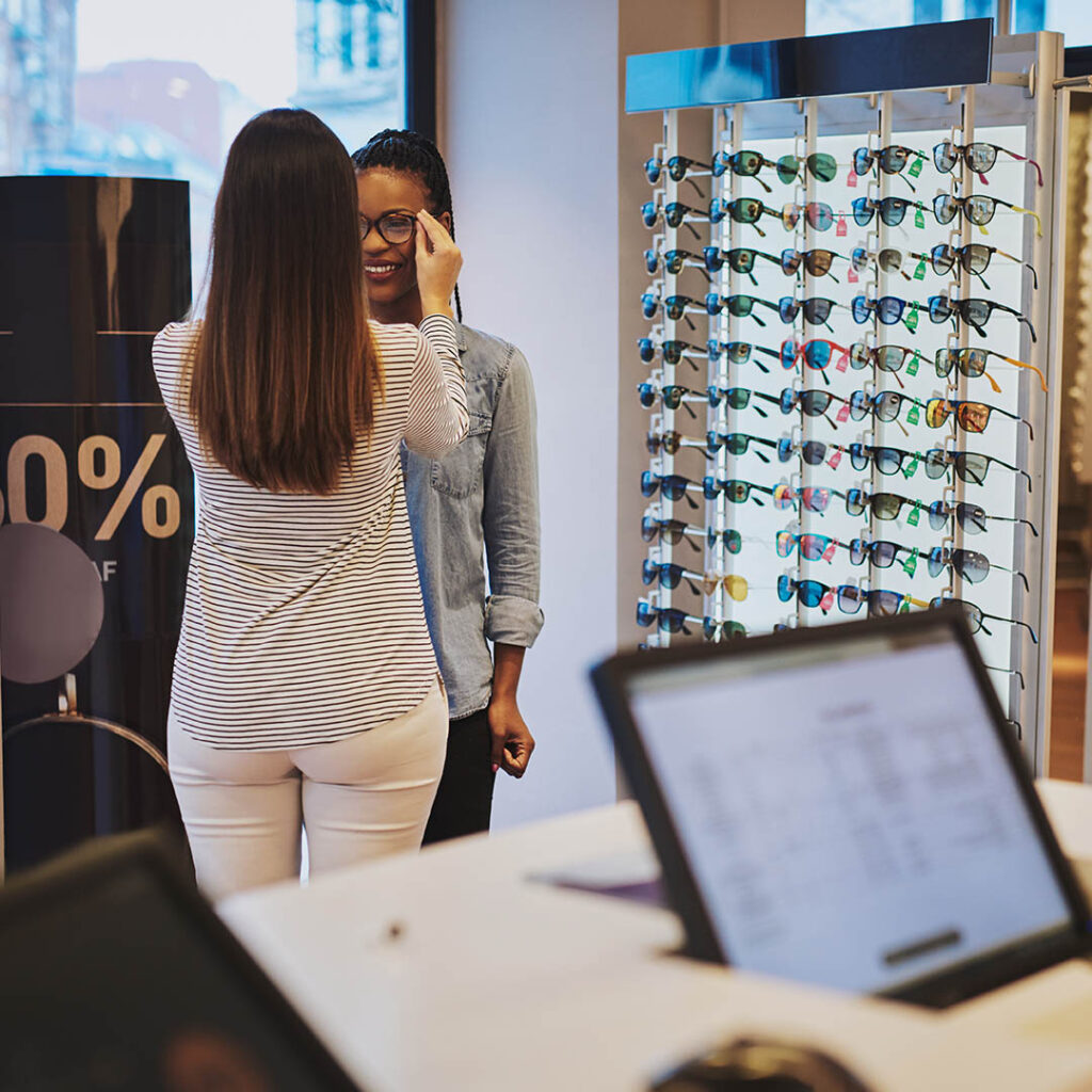 Photo of saleswoman helping a customer who found their eyeglass boutique online via a business directory listing.